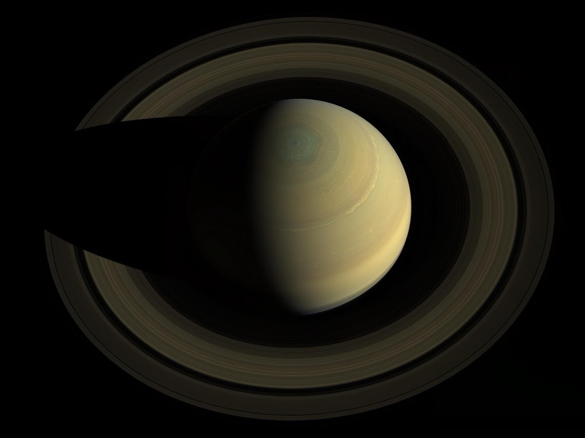 The book includes beautiful views of Saturn. This image shows the planet's north pole and its hexagonal blue-yellow storm, which is big enough to fit several Earths inside.