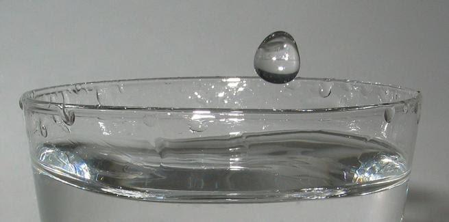 Uma gota d'água caindo na água em um copo