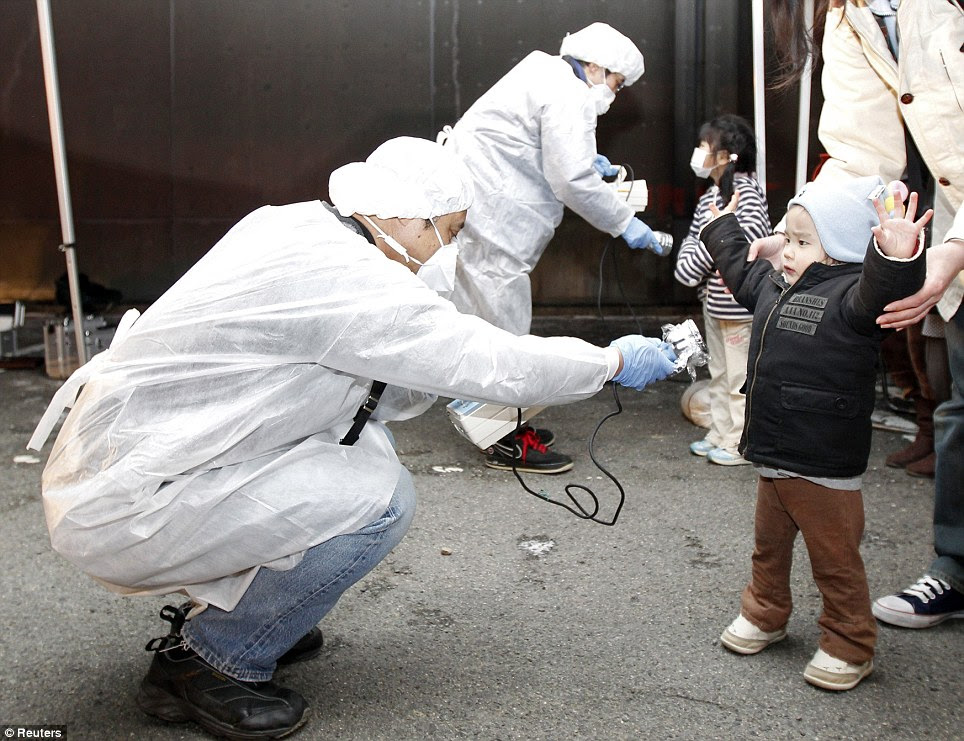 Precaution: Officials in protective gear check for signs of radiation on children from the evacuation area near the nuclear plant