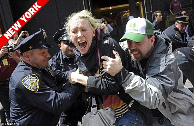 Clash: One protester is caught by police in New York as thousands of activists marched through the city