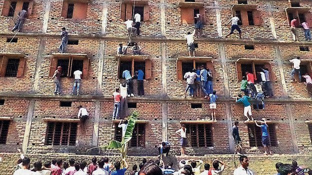 Indians climb the wall of a building to help students appearing in an examination in Hajipur, in the eastern Indian state of Bihar