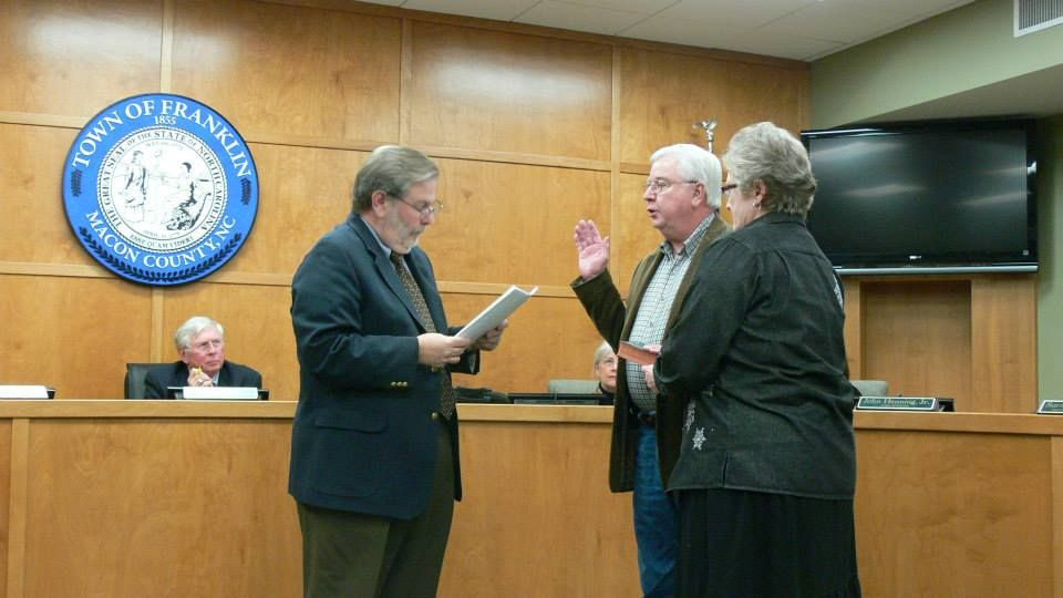 Vic Perry swears in Billy Mashburn for another term as Alderman while his wife looks on