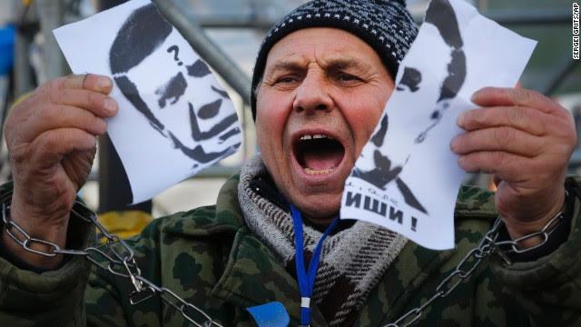 A demonstrator holds a torn portrait of Ukrainian President Viktor Yanukovych on November 29.