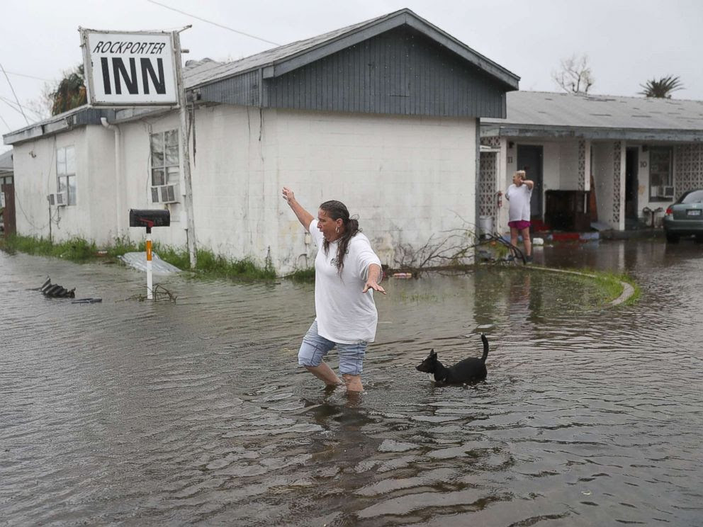 PHOTO: Valerie Brown walks through a flooded area after leaving the apartment that she road out Hurricane Harvey in, Aug. 26, 2017, in Rockport, Texas.