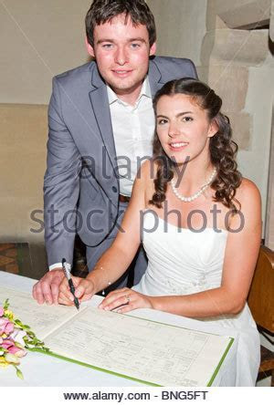bride and groom signing marriage certificate during an