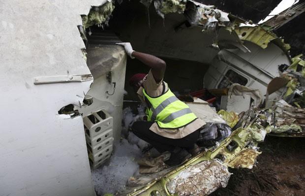 Resgatista inspeciona restos do avião acidentado no aeroporto de Lagos, nesta quinta (3) (Foto: Sunday Alamba/AP)