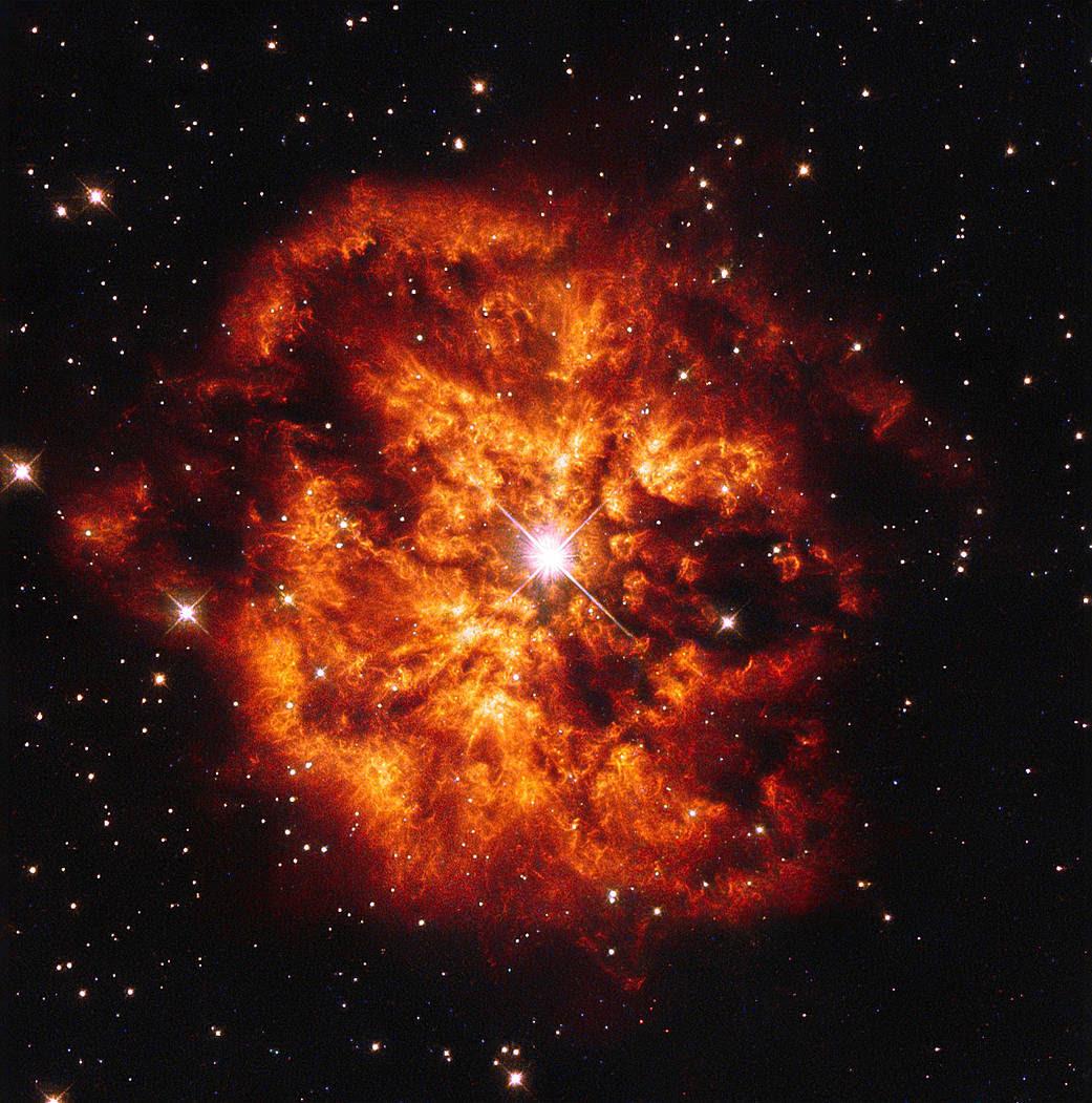 An orange nebula surrounding a bright star on a black background