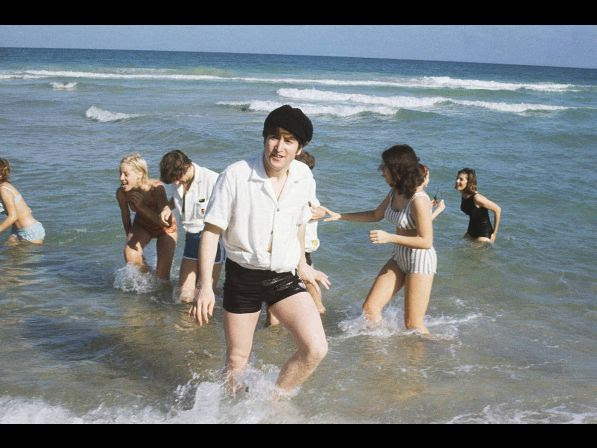 John Lennon of the Beatles emerges from the surf at Miami, Florida in February 1964. In background, left, is Ringo Starr with an unidentified woman. Others are unidentified.