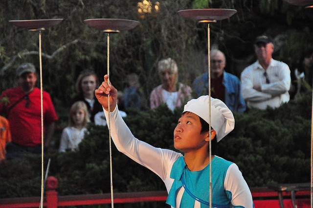 Chinese juggler spinning plates on poles