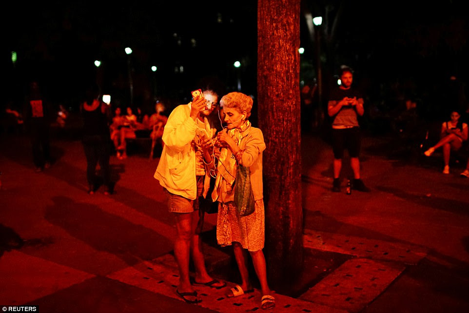 People connect to the internet at a hotspot in Havana, Cuba, on January 19. Internet access is illegal in private homes, but the government-owned cafes and public spaces offer internet access. The web in the communist country is characterised by high cost and censorship