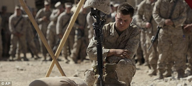 Silent tribute: U.S. Marine Corporal Braxton Russell pays his respects to Lance Cpl. Bernard during a memorial service in Afghanistan