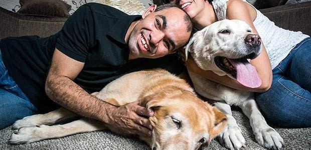 Genival e Kátia estão sorrindo, abraçados com seus cães-guias.