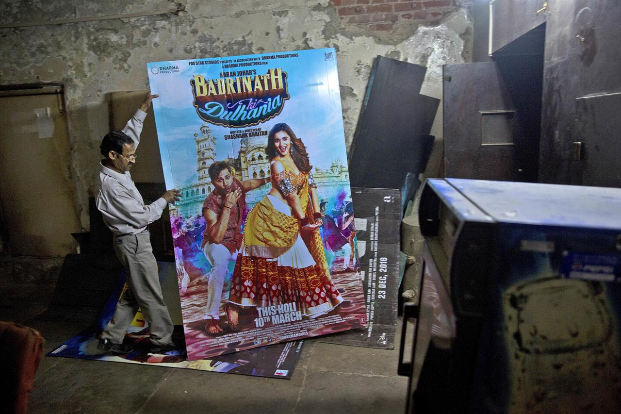 In this Tuesday, March 28, 2017 photo, an employee places a poster of a Bollywood film in the dump room of Regal Theater in New Delhi, India. The Indian capital's iconic theater signed off on Thursday night after more than eight decades with nearly 600 movie buffs cheering a 1964 Bollywood classic at a final screening. It's expected to make way for a multiplex from a single screen.
