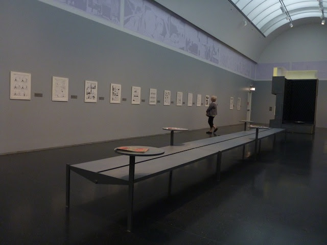 The installation features comics for readers to flip through. At the far end, there's even a bed.