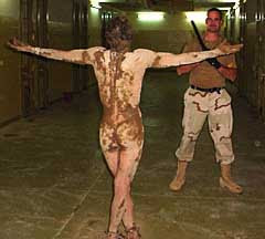 A deranged Abu Ghraib detainee wanders the halls covered in human feces on December 12, 2003. MP Ivan Frederick stands behind him with a stick.