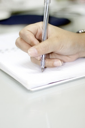 female writing on a notebook Stock Photo - 12982452