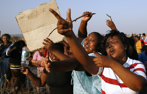 Unidentified women hold a placard that reads Piega come Piega (Phiyega)  as they protests against the police near a shooting scene at the Lonmin mine near Rustenburg, South Africa, Friday, Aug. 17, 2012. by Pan-African News Wire File Photos