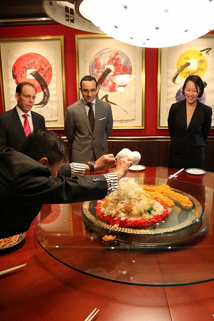 Manager Mr Ng pours the various sauces onto the yusheng
