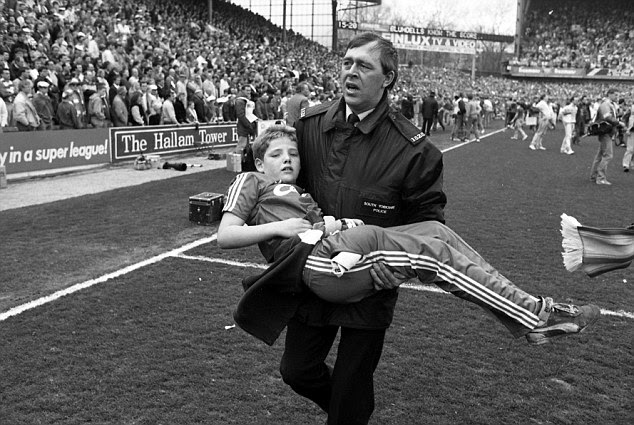 A young Liverpool fan is carried away from the danger as supporters are forced on to the Hillsborough pitch