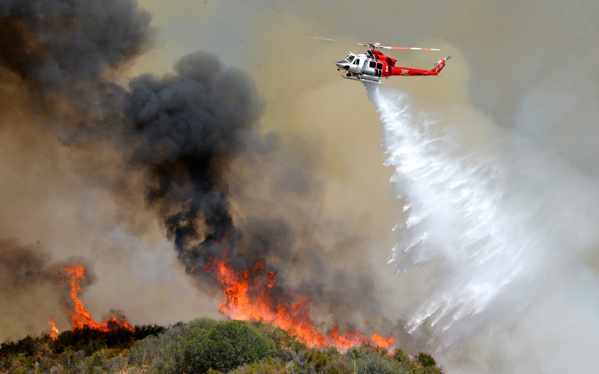 A Los Angeles City Fire helicopter drops water on a wildfire in Santa Clarita, Calif. About 1,000 people have been evacuated from homes as a 100-acre wildfire burns through brushy canyonlands north of Los Angeles