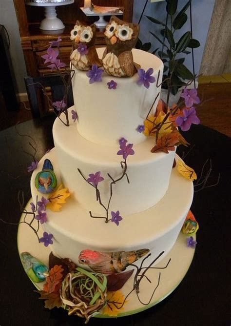Tri tier round white wedding cake with birds and flowers