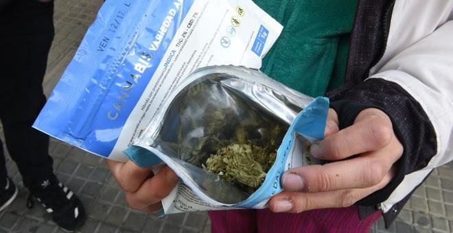 Un hombre muestra un sobre con marihuana comprada en una farmacia de Montevideo /AFP (MIGUEL ROJO)