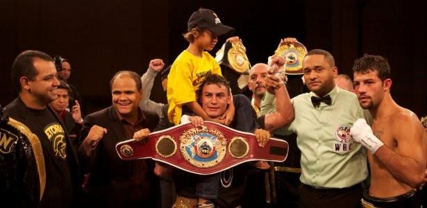 Popó posa com seu filho e seus cinturões após nocautear Michael Oliveira no Uruguai