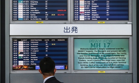 A man looks at a screen displaying 'Pray for MH17'' at Kuala Lumpur International Airport (KLIA) in Sepang outside Kuala Lumpur.