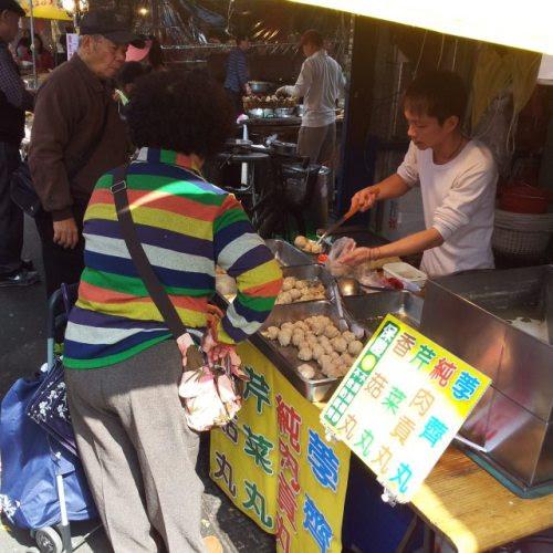 Taipei: To buy some foodstuffs for pot dishes tonight at open-air market.台北:正月も八日目 賑わいを取り戻した青空市場数日前からケータイは今日は晴れ、今日は晴れといっている。布団カバーとシーツを洗濯せねば…朝起きると曇り空です。朝食にお粥をと準備していると日が射して来ました。洗濯機にぶっこみます。夜は鍋、そう決めていたので市場に買出しに出かけます。にぎやかでした、とても。昨夜、切れた薩摩芋をと市場に来てみると、空っ風しかおりません。今日は陽射しがあって、暖かで、にぎやかで、市場日和です。鍋用に芋頭、あげ豆腐、ガンモドキ、魚丸を手に入れました。人でごった返した市場の路地、杖をつくオバーちゃんに出くわすと動きが滞ります。私の後ろの方々もそれに習えです。スクーターも立ち往生。奇麗に化粧したお嬢サンが、小型カメラで肉の塊、臭豆腐の煮込み、山積みされた果物の山にレンズを向けています。聞こえてきたおしゃべりは日本語。路地の中央に位置する文昌廟あたりは若い連中が熱心に拝拝しています。いつもの風景とはいえ、いつ見ていても飽きない青空市場です。一軒の出店、ボードには茡薺丸 (水栗、菱の実)純肉貢丸 (肉だけの団子か)芹菜丸 (セリ菜) 香菇丸 (きのこ)今夜の鍋にと思ったのですが、すでにあげ豆腐、魚丸を購入済です。またの機会に…