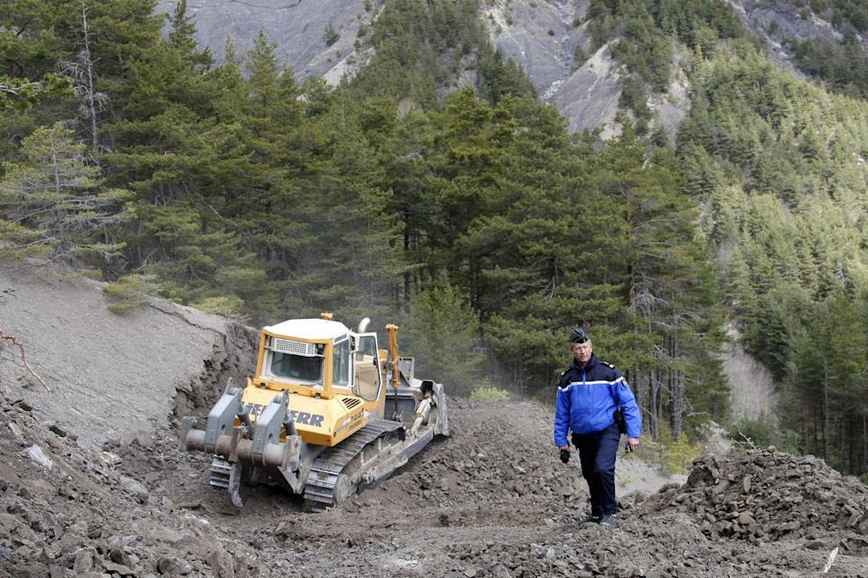 Gendarme Bruno Hermignies stands by a bulldozer clearing a path to the crash site near Seyne-les-Alpes, France, Monday, March 30, 2015.  European...