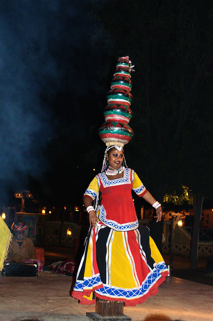 Dancing on a bed of wooden nails, with pots on her head