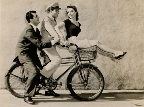 Dean Martin, Dewey Martin and Anna Maria Alberghetti ride a bike.