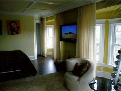 Master bedroom; view is toward bay window and walk-in closet.  Note flat-screen