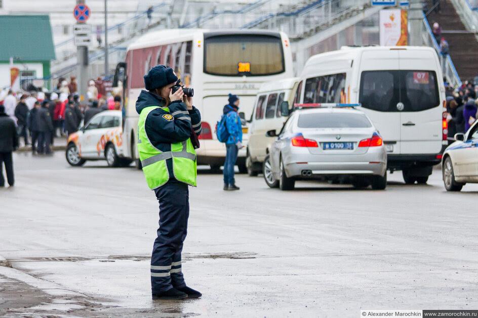 Девушка инспектор с фотоаппаратом на эстафете Олимпийского огня в Саранске