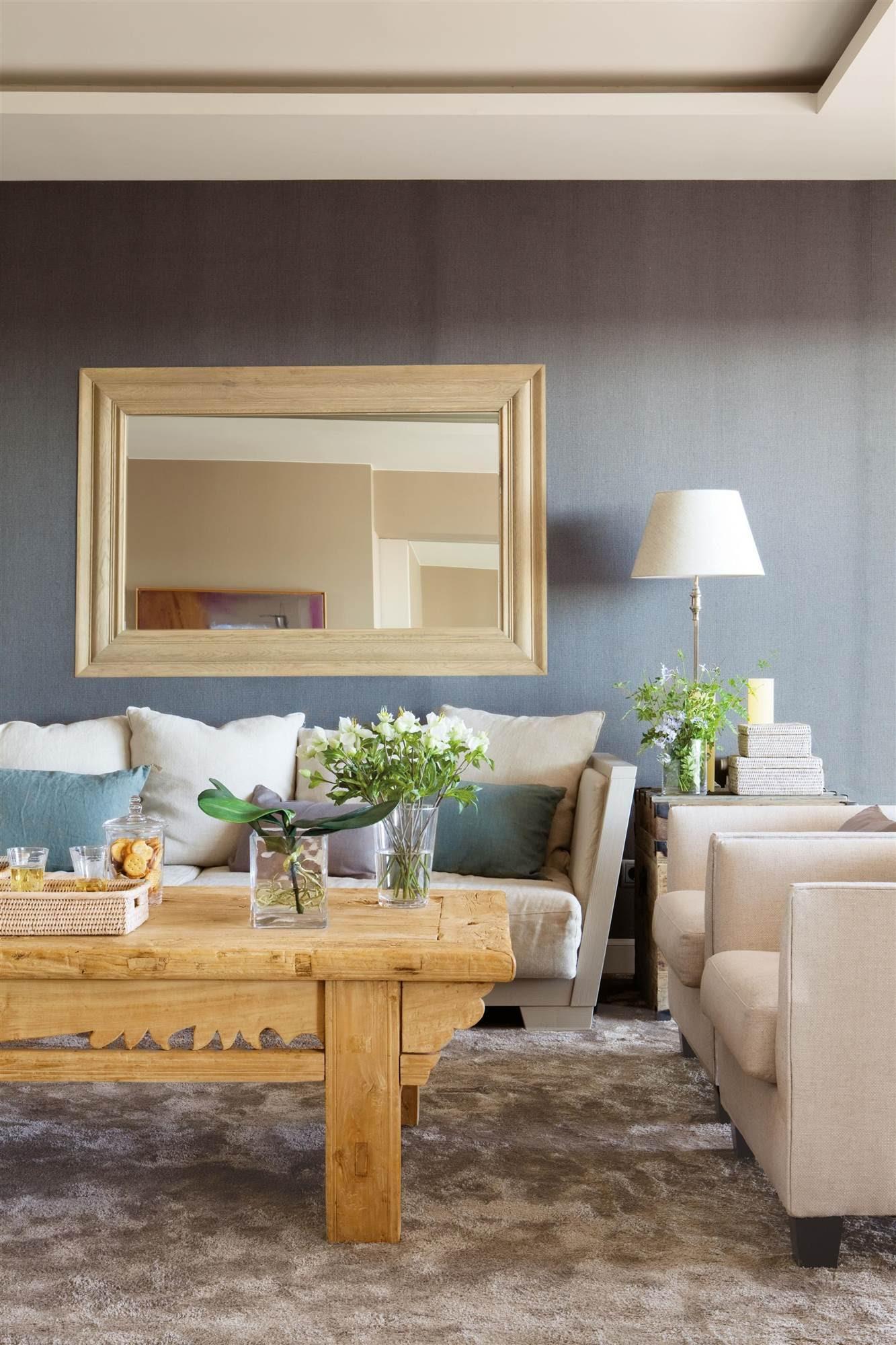 00323753. Salón con pared enterada con seda, con un espejo sobre el sofá tapizado con lino y mesa de centro de madera de olmo altiguo_ 00323753