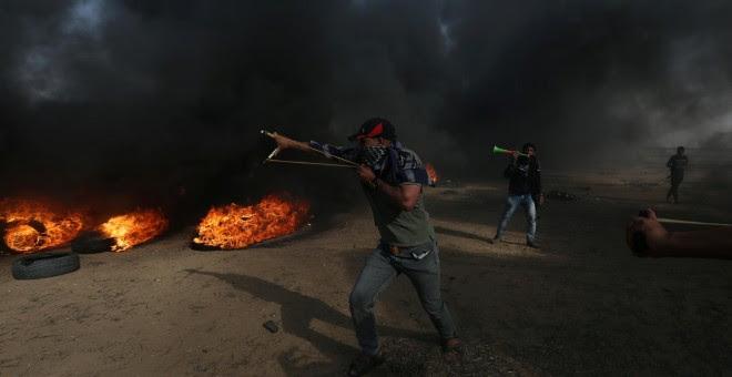 Un manifestante usa un tirachinas para arrojar piedras durante una protesta en la que los palestinos reclaman el derecho a regresar a su patria, en la frontera entre Israel y Gaza. REUTERS / Ibraheem Abu Mustafa