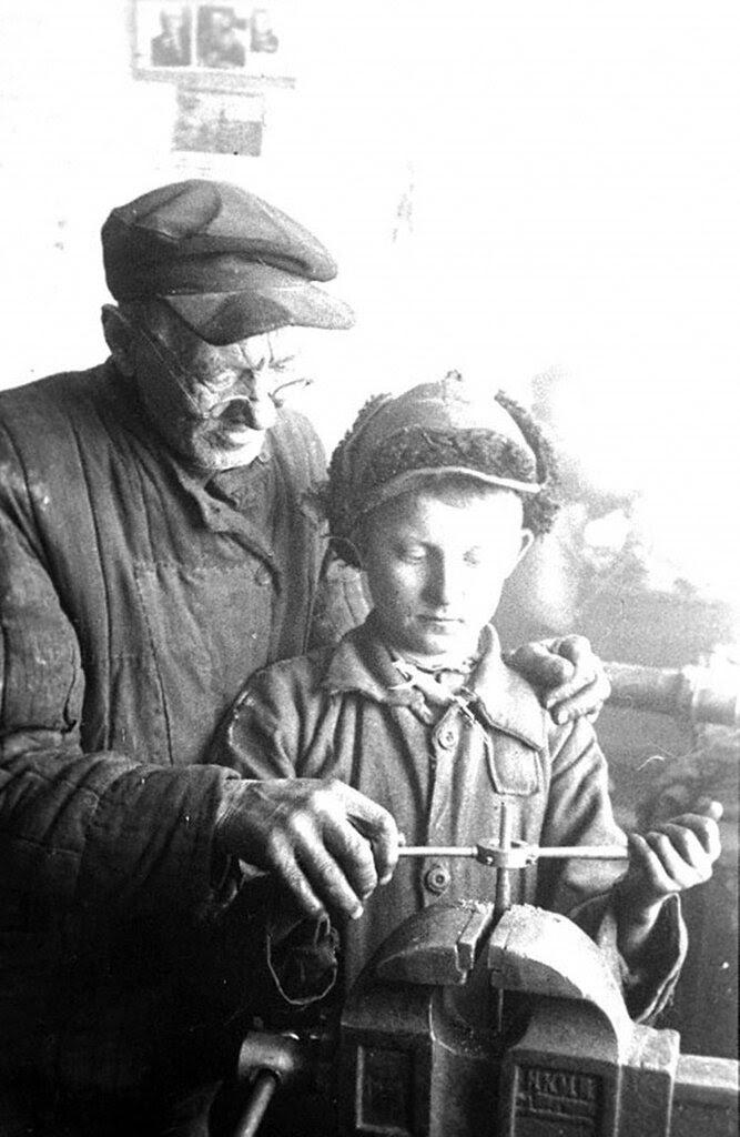 Ученик Новоузенской МТС К.Варыпаев под руководством своего наставника слесаря И.В.Негодина обучается нарезке винта. 1943 г. Саратовская область.