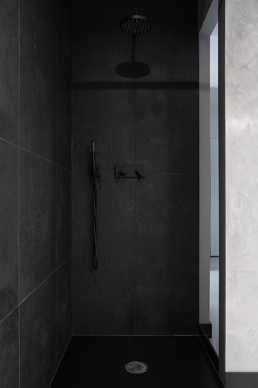 Stylish shower area clad in black tiles