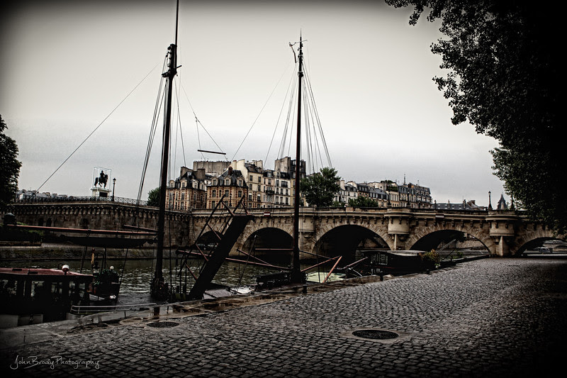 A Little Rain And The Crowds Disappear - At Pont Neuf Bridge, an area usually swarming with people, on the Banks of the River Seine in Paris, France - JohnBrody.com - JohnBrody.blogspot.com
