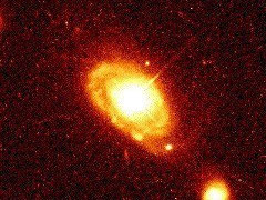 Figure 2. Image showing the luminous quasar-like core of spiral galaxy PG 0052+25. Taken with the Hubble Space Telescope.  (Courtesy of J. Bahcall and NASA)