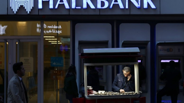 File Photo: A street vendor in front of the Turkish Halkbank, in Istanbul. Mehmet Hakan Atilla, 47, a deputy manager at Halkbank, has been found guilty by a federal court in New York of participating in a major scheme in which Iranian gold and gas where traded for food and gold. EPA, SEDAT SUNA