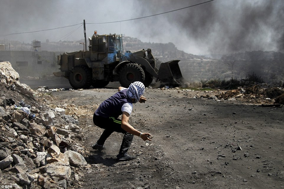 Palestinian protester hurls stones at Israeli  army bulldozer during clashes which following a protest against Israeli settlements in Qadomem