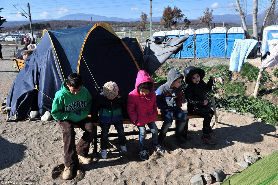 Children wait with other migrants and refugees to cross the Greek-Macedonian border near the village of Idomeni, northern Greece