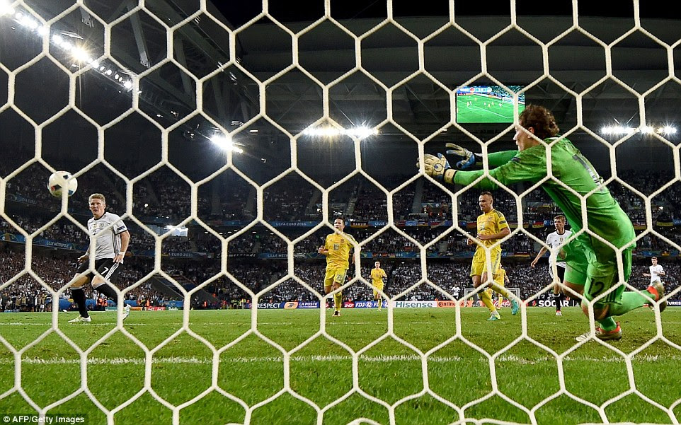 Schweinsteiger, 31, (left) watches as his shot finds the back of the net, past Ukraine's 31-year-old goalkeeper Andriy Pyatov (right)