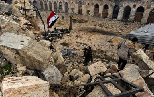 A member of forces loyal to Syria's President Bashar al-Assad attempts to erect the Syrian national flag inside the Umayyad mosque, in the government-controlled area of Aleppo, during a media tour, Syria December 13, 2016. REUTERS/Omar Sanadiki
