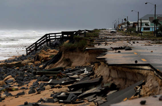An official vehicle navigates debris as it passes along Highway A1A after it was partially washed away by Hurricane Matthew on Oct. 7, 2016, in Flagler Beach, Fla.