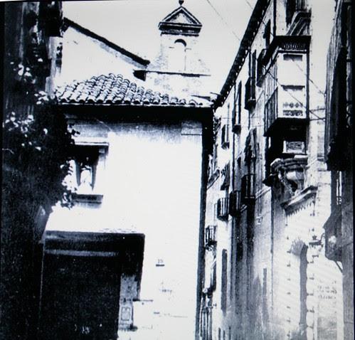 Calle Cadenas de Toledo con la puerta del Banco de España frente a la entrada de la iglesia de San Nicolás