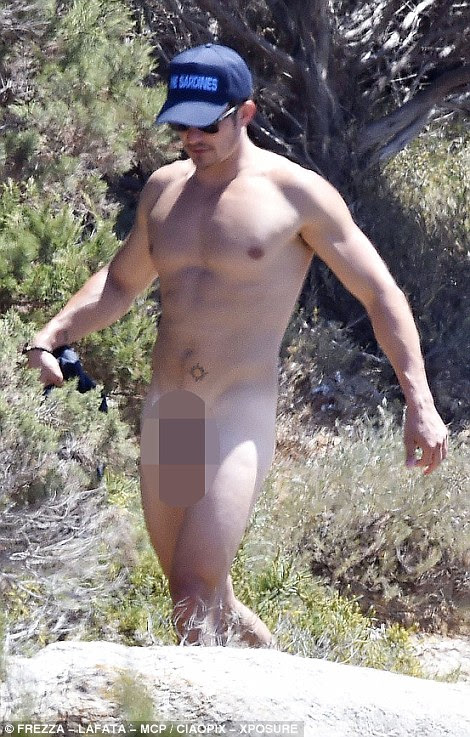 Easy does it! As he came back to shore with his shorts in hand, the athletic actor moved nimbly over the rocky terrain