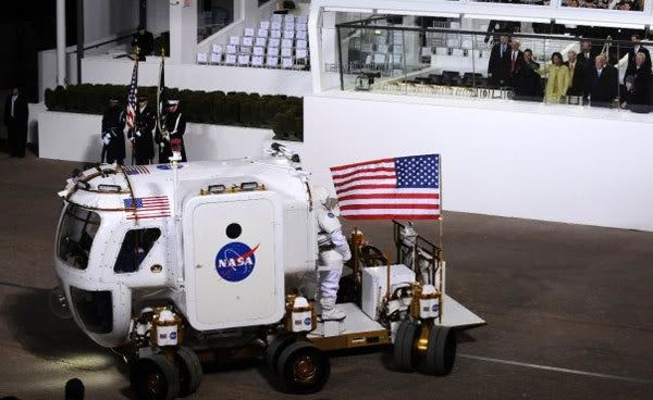 President Obama and his wife Michelle look on from within the reviewing stand as NASA displays its Lunar Electric Rover, during last night's Inaugural Parade in Washington, D.C.