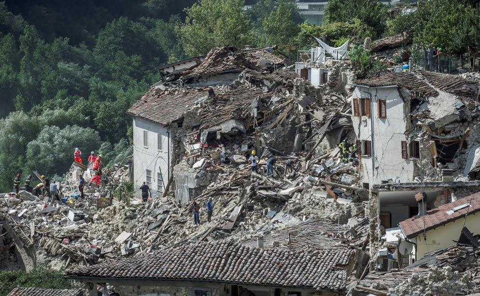 Equipos de emergencia buscan supervivientes entre los escombros causados por un terremoto en Pescara del Tronto (Italia).